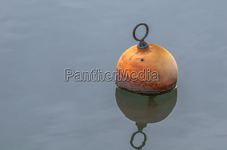 mooring buoy reflecting on calm water