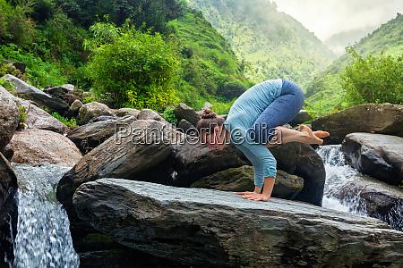woman doing bakasana asana outdoors
