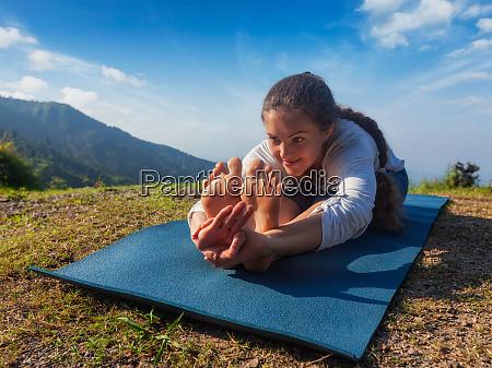 woman doing yoga asana paschimottanasana forward