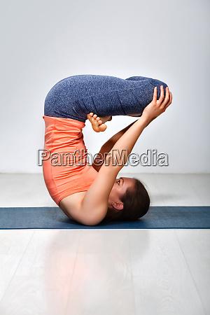 woman practices inverted yoga asana