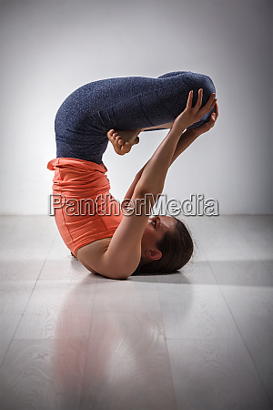 sporty fit woman practices inverted yoga