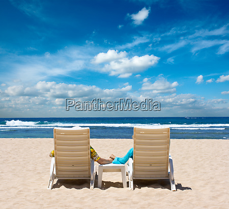 couple in beach chairs holding hands