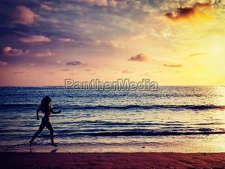beautiful athletic woman running along sea