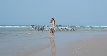 woman walk on beach and look