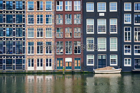 amsterdam canal damrak with houses netherlands