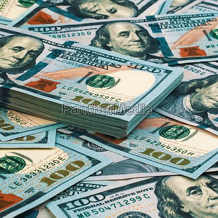 background of scattered hundred dollar bills