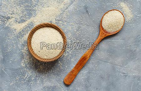 raw uncooked fonio seeds grey background