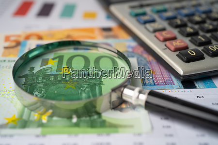 eyeglass with calculator on euro banknotes