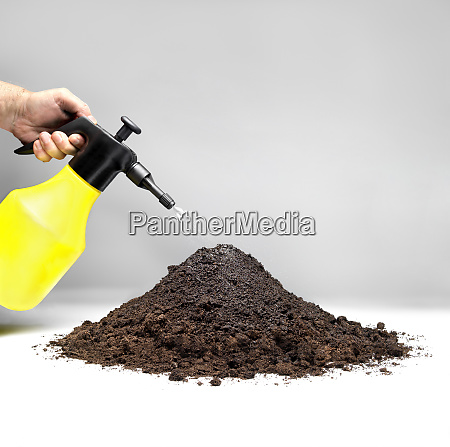 hand irrigating a pile of soil