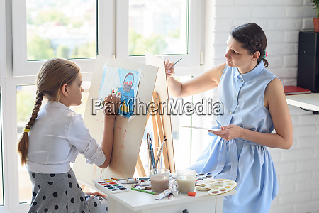mom and daughter draw on easels