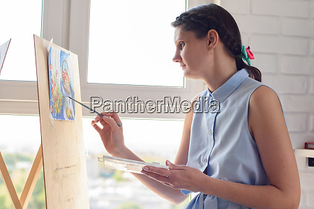 girl draws with brushes and watercolors