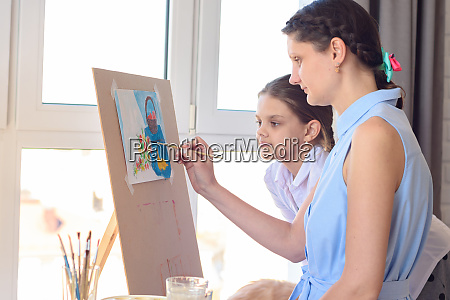 daughter watches mom draw on an