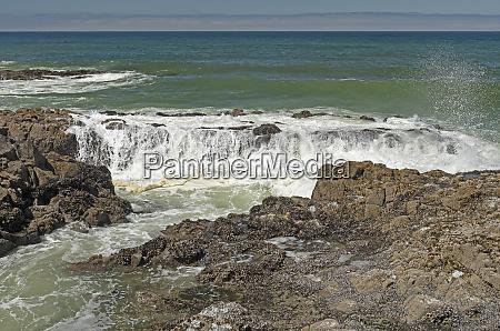waves pouring over coastal rocks