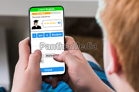 boy typing text message on mobile