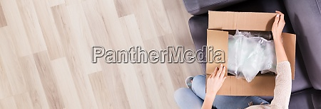 woman opening delivered parcel