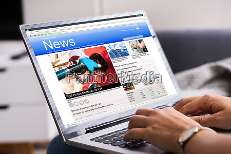 reading online news website on computer