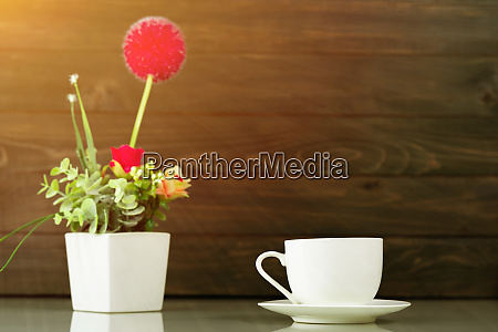 coffee cup and artificial flower vase