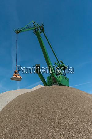 green green grab crane fills sand