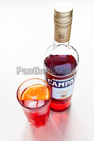 glass with cocktail and closed bottle
