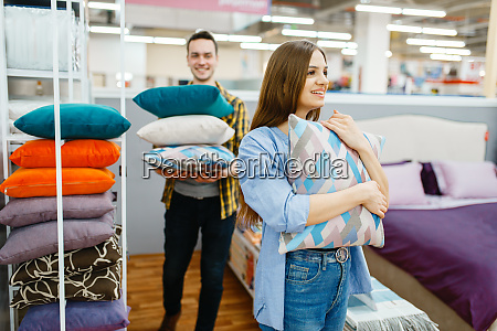 love couple holds pillows in furniture