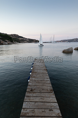 wooden pier and sailboats sailing in