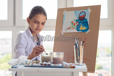 girl sits behind an easel and