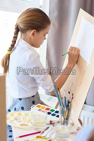 girl is focused on drawing with