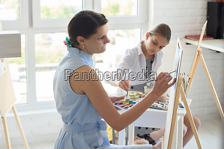 concentrated girl draws on easel next