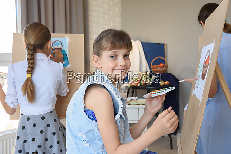 girl smiles sitting at easel with