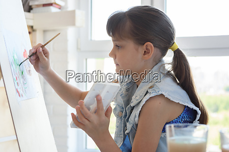 girl diligently draws a picture on