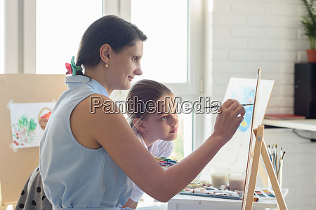 drawing teacher shows girl how to