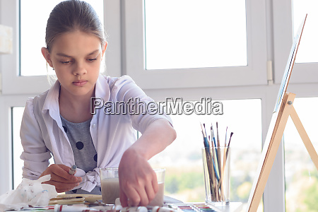 girl examines paint in the workplace
