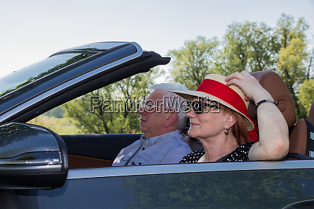 older couple drives with a luxury