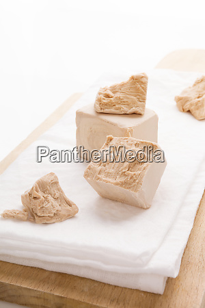 fresh yeast blocks on wooden board