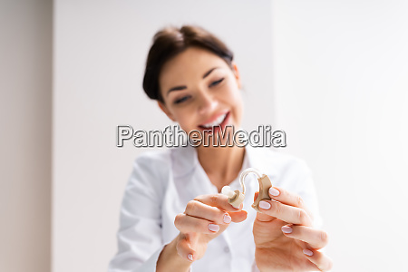 female doctor showing hearing aid