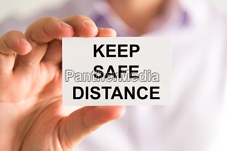 businessman holding keep safe distance message