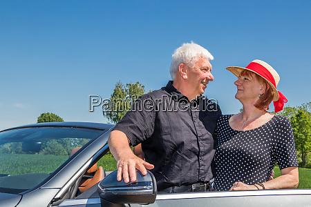 senior couple in convertible car enjoying