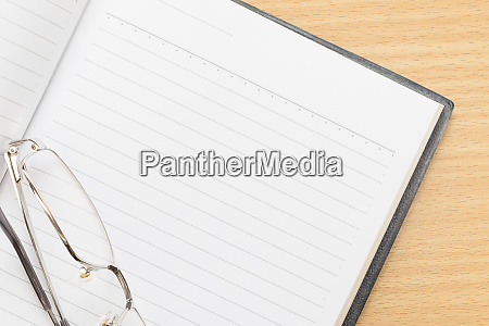 notebook open blank page and eyeglasses