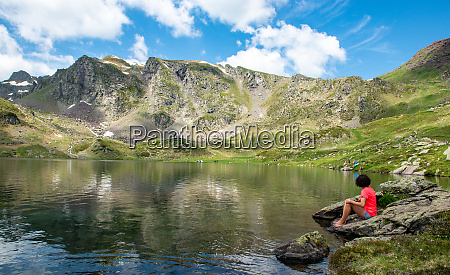 hiker rests by a lake in