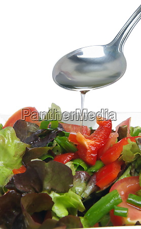 adding oil to salad
