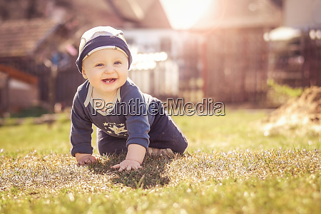 an infant crawls on the lawn