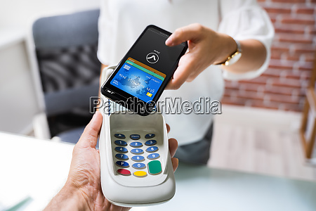 paying with mobile phone to cashier