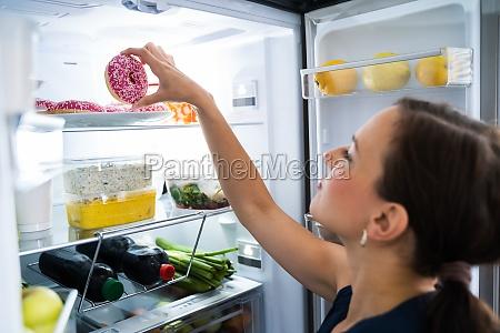 woman on diet indulging in kitchen