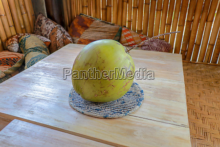young green coconut on teak table