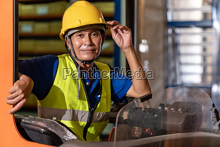 asian warehouse worker with forklift in