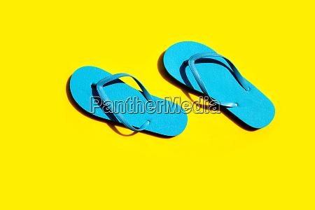blue flip flops on yellow background