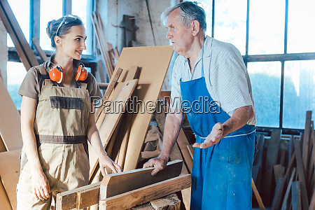 senior carpenter sharing wisdom with younger