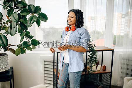 cheerful woman in headphones listening to