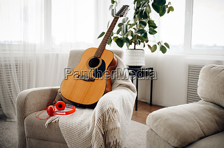 guitar and headphones on white armchair