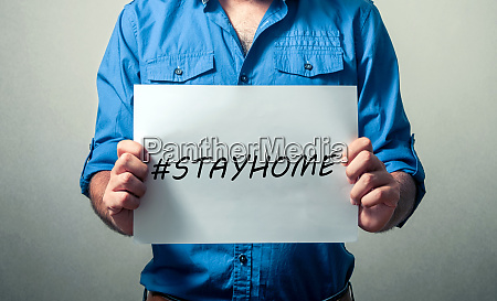 man holding stay at home sign
